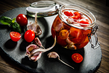 Tomatoes in jar on wooden background