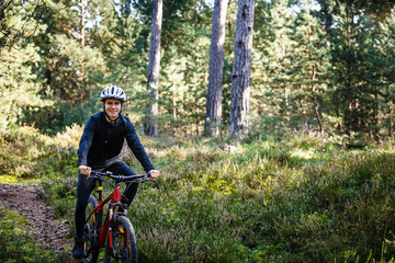 Young man biking in forest