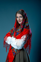 Russian beauty woman in the national patterned shawl on blue grey background. Maslenitsa