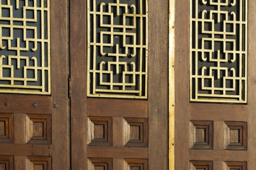 Oriental style window grill features on the doors of a Chinese restaurant in London, UK