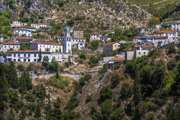 """Panorama of Dhermi - attractive mountain village with school building (in albanian language """"shkolla"""") church and houses sticking on the slope, Albania, Europe"""