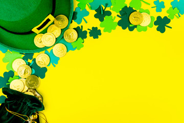 Saint Patrick's Day. Little bag with gold coins, green three petal clover, green hat of leprechaun on yellow background Wall mural