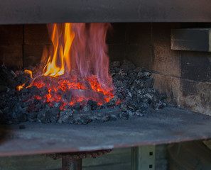 Fire blazes inside the dark coal forge heating up metal to become a set of spurs.