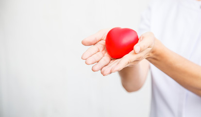 Selective focus of red heart held by female nurse's hand, representing effort to deliver high quality service mind to patient. Professional, Specialist in white uniform isolated on white background.