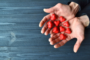 Male hands with red candies in a form of heart on the dark blue wooden background.