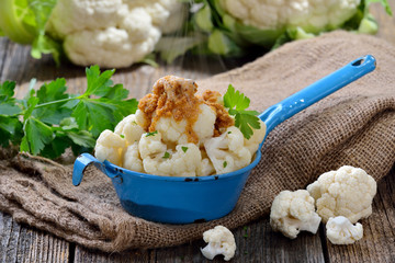 Gegarter Blumenkohl mit in Butter gebräunten Semmelbrösel im Shabby-Emailletopf dampfend serviert – Cooked cauliflower topped with breadcrumbs browned in butter and served steaming hot  in an old pot
