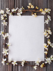 Blossom branch frame (apple tree flowers)  with white blank greeting card on wooden background. Spring blooming.