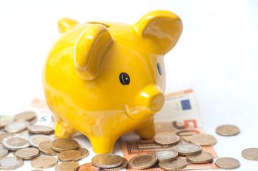 tirrelire jaune en forme de cochon et euros en billets et pièces de monnaie