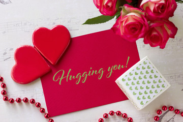 Valentines day greeting card with roses gift box hearts and lettering hugging you.