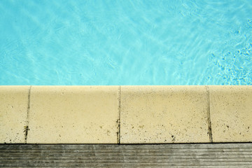 Decking and stone edging detail around a swimming pool