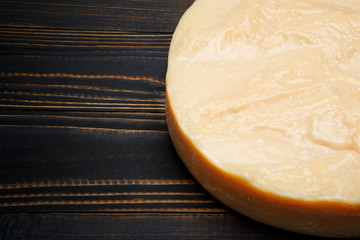 Whole round Head of parmesan or parmigiano hard cheese on wooden background