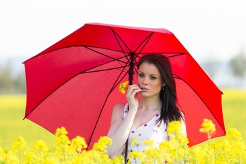 Beautiful young woman with sunblock or rainy weather umbrella . Beautiful girl with finger and flower at lips in yellow flowers field. Country life lifestyle because of rain or solar sun protection