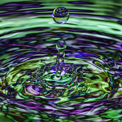 Water droplet with a multi coloured blue green iridescent transparent ripple splash