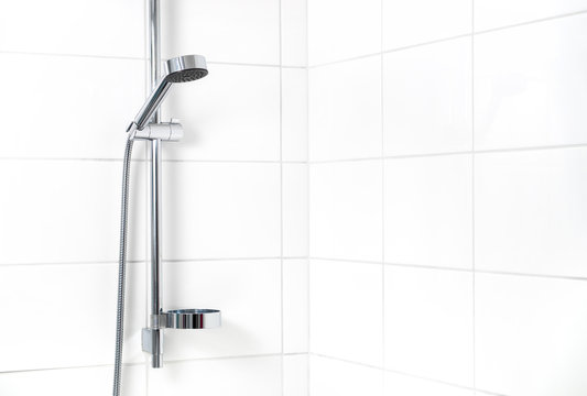 Modern shower with white wall tiles. Simple stylish Scandinavian home interior design. Clean fresh bathroom.