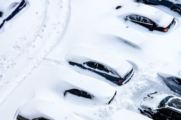 After a snowstorm, cars in the parking lot are covered with a thick layer of snow