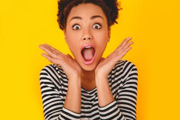 Young african woman isolated on yellow wall studio teen style shocked