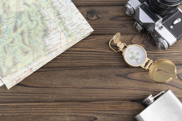 retro camera, map, compass, flask on a wooden background with copy space. travel, tourism. leisure.