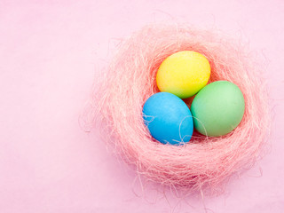 Color easter eggs in pink nest on pastel background.