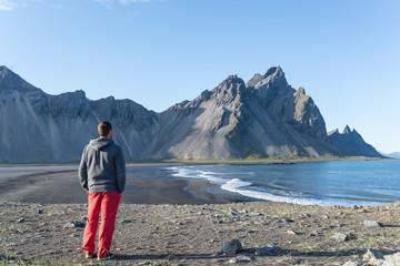 Hombre joven mirando la playa volcánica de la península de Stokksnes en Islandia.