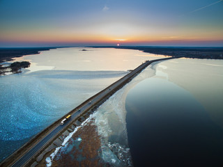 Aerial view of road in the frozen lake with moving cars on sunset.