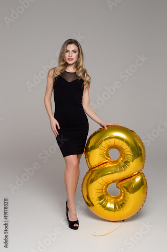 51bd50559d92 Sexy, beautiful girl in black dress is holding big golden 8-shaped balloon.  Grey background. Happy woman's day