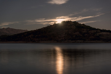Night landscape view of full moon over lake.