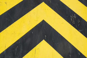 Black and yellow steel surface of industrial equipment. Warning or danger pattern.