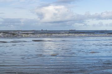 Low tide at Scheveningen beach near the Hague featuring cargo ships on horizon under dark sky clouds.
