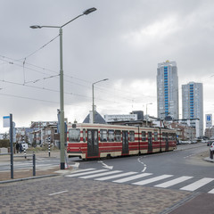 Details of street infrastructure with pedestrian crossing and bicycle lane and tram car crossing street in the Hague, Netherlands.