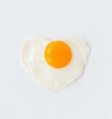 fried egg in heart shape on a white plate love