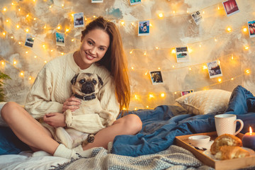 Young woman weekend at home decorated bedroom hugging a dog