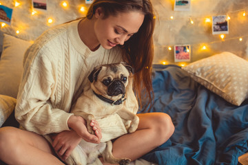Young woman weekend at home decorated bedroom holding paw of dog