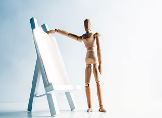 A wooden man with an easel.