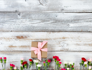Colorful carnation flowers and gift forming bottom border on white weathered wooden boards