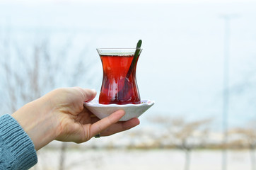 Woman holds a glass of Turkish tea