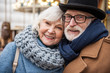 Portrait of joyful senior married couple hugging while relaxing outdoor