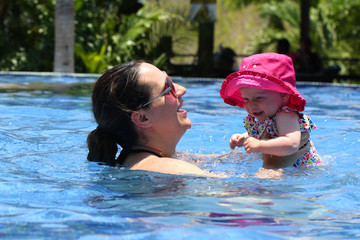 Mother in sunglasses and eight month old daughter in pink hat looks at camera and swim at the pool at Costa Rica Resort. Concept of happy friendly family enjoying family time. Positive human emotions