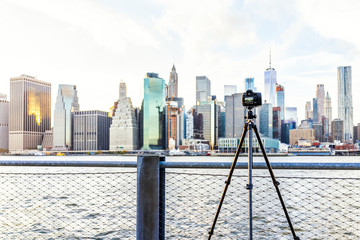 Camera, tripod set up outside outdoors in NYC New York City Brooklyn Bridge Park by east river, railing, taking pictures of cityscape skyline during sunset