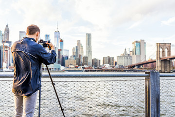 Back of young man photographer with camera, tripod setting up outside outdoors in NYC New York City Brooklyn Bridge Park by east river, railing, looking at view of cityscape skyline
