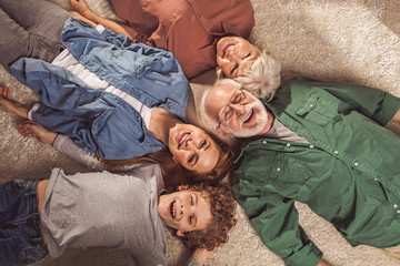 Top view portrait of cheerful bearded grandfather, outgoing grandma, beaming lady and glad son lying on floor. Family concept