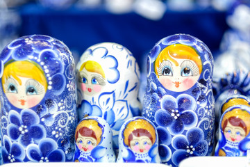 A lot of blue Matryoshka at souvenir market shop. Different colors Russian dolls. Traditional classic Russian handicraft art background. Famous classical and modern Russian dolls Matryoshka toys