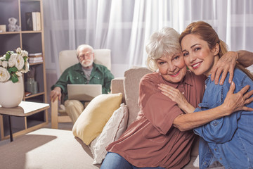 Portrait of glad grandmother hugging smiling woman. They looking at camera while sitting on sofa. Family concept