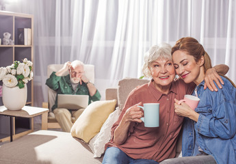 Portrait of happy grandmother hugging young woman. They tasting mug of beverage. Family concept