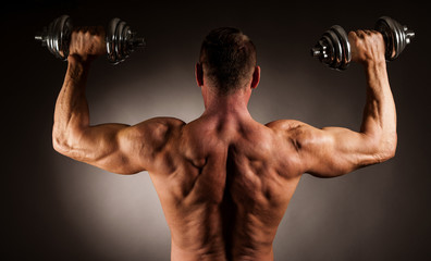 Strong male athlete works out with dumbbells in studio over dark backgound
