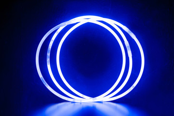 blue round bracelets/ Three round bracelets of glow sticks of blue with neon glow. With reflection on a black background