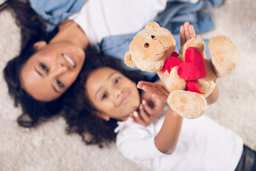 Top view portrait of glad mom and daughter relaxing on the warm carpet. Focus on childs hands holding toy