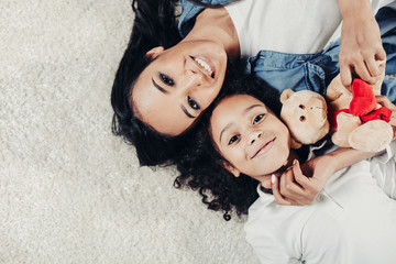 Top view portrait of content mother and child resting on rug with teddy bear. Copy space in left side