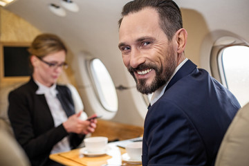 Portrait of contented middle aged male in airplane with his colleague sitting in front of him, he is looking at camera with broad smile. Focus on man