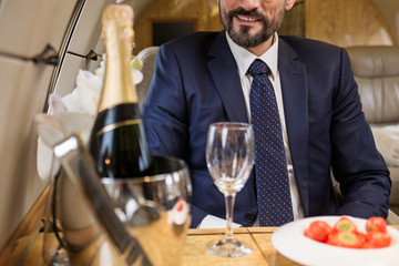 Smiling bearded male sitting in airplane seat at tray table with champagne and strawberry. Focus on man Fototapete