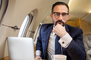 Portrait of serious handsome male in aircraft cabin sitting in his seat and looking at camera